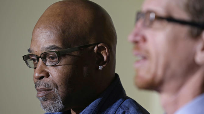 FILE - In this Jan. 15, 2013 file photo, Alton Logan, left, who spent 26 years in prison for a murder he didn't commit, looks on as his attorney Jon Lovey speaks at a news conference in Chicago. On Thursday, Jan. 17, 2013, the Chicago City Council voted to approve paying $32 million to settle police lawsuits. The council agreed to pay $10.25 million to Logan and $22.5 million to a woman who was raped and fell from a seventh story window after she was released from police custody even though she was clearly mentally ill. (AP Photo/M. Spencer Green, File)