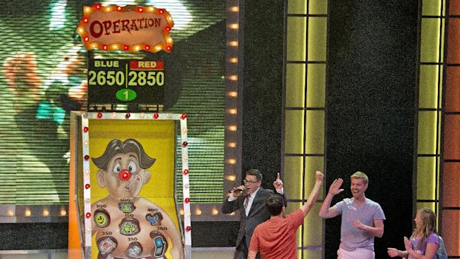 "In this June 18, 2012 photo provided by Carnival Cruise Lines, guests aboard the Carnival Breeze celebrate their team's victory during a giant rendition of Operation during ""Hasbro, The Game Show,"" where vacationers are part of a pretend television show through a series of larger-than-life productions based on Hasbro's iconic games. (AP Photo/Carnival Cruise Lines, Andy Newman)"