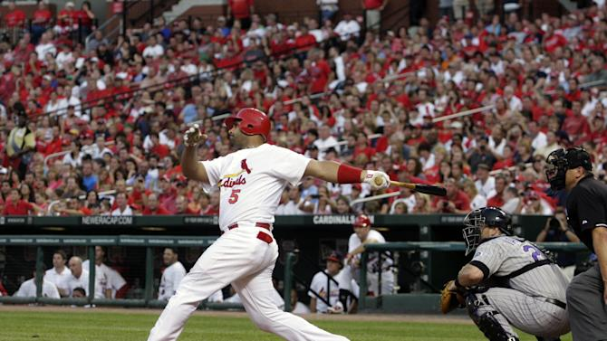 St. Louis Cardinals first baseman Albert Pujols is joined by Colorado Rockies catcher Chris Iannetta and home plate umpire Chad Fairchild as they watch his two-run home run in the first inning of a baseball game, Sunday, Aug. 14, 2011, in St. Louis. (AP Photo/Tom Gannam)