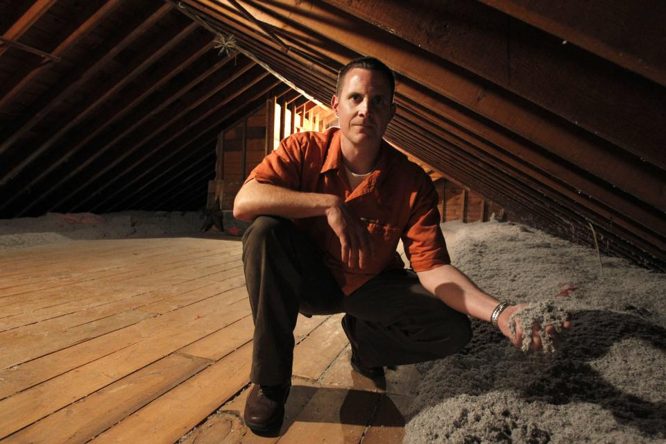 CORRECTS SPELLING OF NAME TO BOTELHO, NOT BOTEHLO - In this June 22, 2011 photo, Stephen Botelho, of Westwood, Mass., holds cellulose insulation in the attic of his home. Botelho installed the cellulose insulation as an energy saving measure. (AP Photo/Steven Senne)