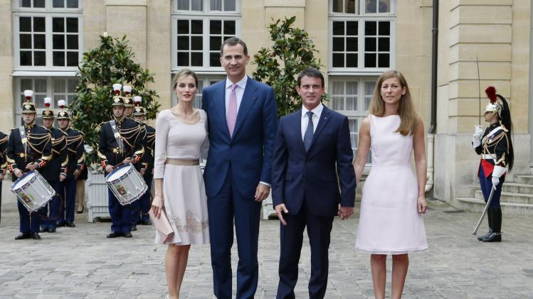 French Prime Minister Manuel Valls and his wife Anne Gravoin welcome Spain's King Felipe VI and Queen Letizia as they arrive at the Hotel Matignon in Paris