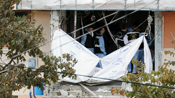 Forensic investigators seen at the entrance of police station after a suicide bomber threw a hand grenade and blew himself up in Istanbul, Turkey's biggest city, Tuesday, Sept. 11, 2012,  killing one police officer and wounding seven other people, authorities said. AP Photo)