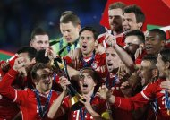 Germany's Bayern Munich Philipp Lahm (bottom C) holds the trophy as he celebrates with his teammates after winning their 2013 FIFA Club World Cup final soccer match against Morocco's Raja Casablanca at Marrakech stadium December 21, 2013. REUTERS/Youssef Boudlal (MOROCCO - Tags: SPORT SOCCER)
