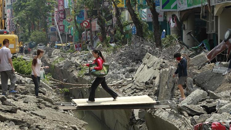 A woman crosses over a trench made from a massive gas explosion in Kaohsiung, Taiwan, Friday, Aug. 1, 2014. Scores of people were killed and more than 200 others injured when several underground gas explosions ripped through Taiwan's second-largest city overnight, hurling concrete through the air and blasting long trenches in the streets, authorities said Friday. (AP Photo/Wally Santana)
