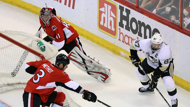 Pittsburgh Penguins' Sidney Crosby (87) looks to pass as Ottawa Senators goaltender Craig Anderson (41) is caught behind the net and Senators' Marc Methot (3) attempts a poke-check during first-period NHL hockey playoff game action in Ottawa, Ontario, Wednesday, May 22, 2013. (AP Photo/The Canadian Press, Fred Chartrand)