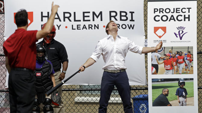 Britain's Prince Harry reacts after hitting a baseball pitched to him by New York Yankees' Mark Teixeira, left, during a visit to the Harlem RBI youth sports and school program in New York, Tuesday, May 14, 2013.  (AP Photo/Kathy Willens)