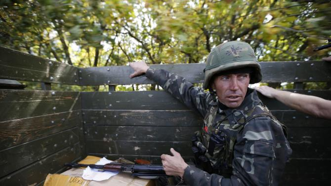 A Ukrainian serviceman rides on a military truck near the eastern Ukrainian town of Pervomaysk