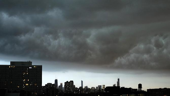 Storm cloud hangs over downtown Chicago skyline Monday, June 30, 2014, as rain and high winds were moving into Illinois from Iowa. Flights cancelled at Chicago's O'Hare International Airport as northern Illinois braces for severeweather. (AP Photo/Kiichiro Sato)