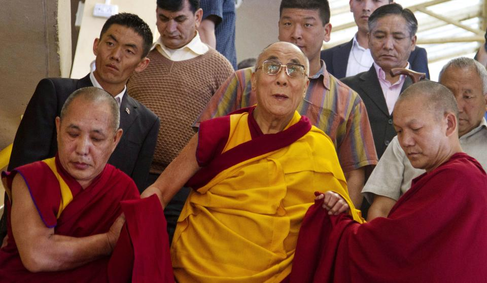 Tibetan spiritual leader the Dalai Lama, center, is helped by monks in descending stairs as he leaves a prayer session in Dharmsala, India, Monday, Sept. 26, 2011. (AP Photo/Ashwini Bhatia)