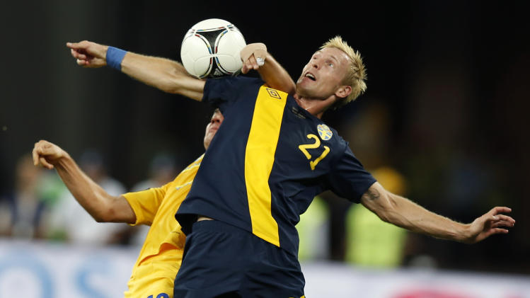 Sweden's Christian Wilhelmsson, foreground, and Ukraine's Serhiy Nazarenko challenge for the ball during the Euro 2012 soccer championship Group D match between Ukraine and Sweden in Kiev, Ukraine, Monday, June 11, 2012. (AP Photo/Sergei Grits)