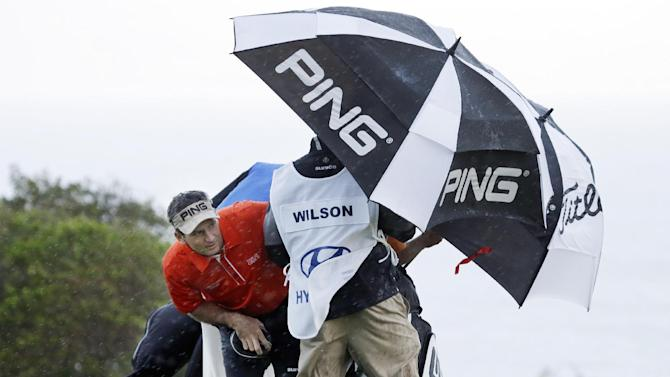 Mark Wilson peers out from under an umbrella as he waits for a rain squall to ease up before teeing off on the 10th hole during the first round at the Tournament of Champions PGA golf tournament, Monday, Jan. 7, 2013, in Kapalua, Hawaii. Play was to have started three days earlier, but was delayed because of rain and high winds. (AP Photo/Elaine Thompson)