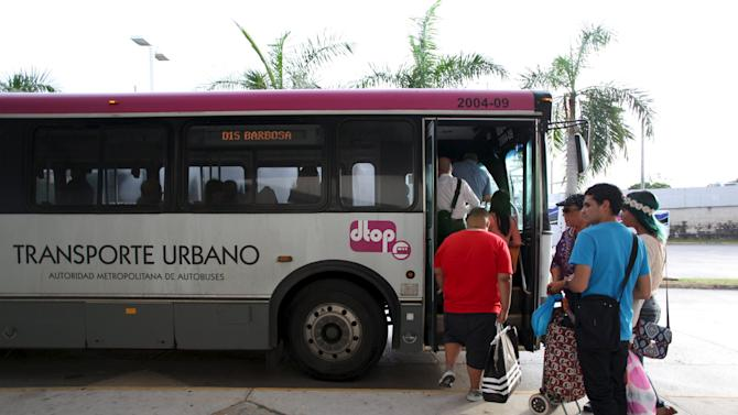 People stand in line to board a public bus in San Juan