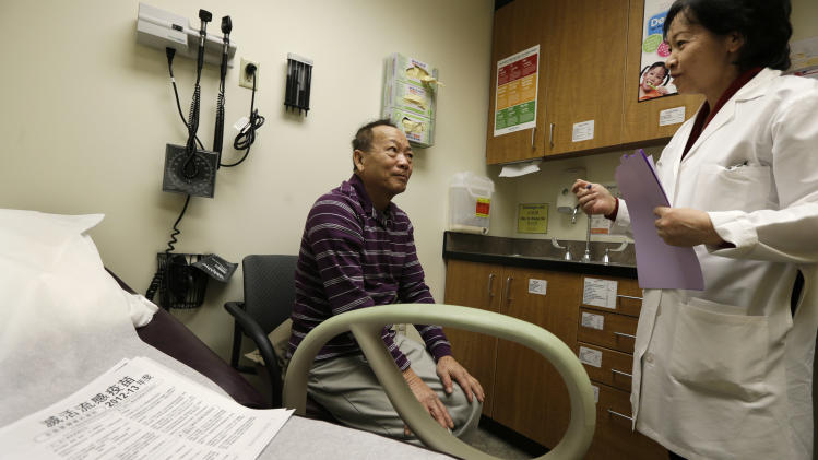 Chan Lai Ly, left, speaks Vietnamese with Cecilia Trinh, right, a medical assistant, during a regular check-up related to his diabetes, Friday, March 1, 2013 at International Community Health Services in Seattle. The clinic, which serves patients who speak more than 50 different languages, illustrates a challenge Washington state will face as it launches its new health insurance exchange as part of the federal Affordable Care Act. (AP Photo/Ted S. Warren)