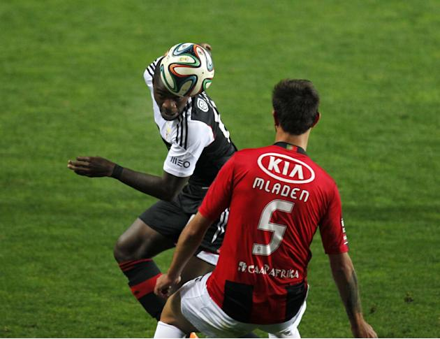 Benfica's Ola John, left, from The Netherlands, vies for a high ball with Olhanense's Sebastian Mladen, from Romania, during a Portuguese league soccer match between Benfica and Olhanense at t