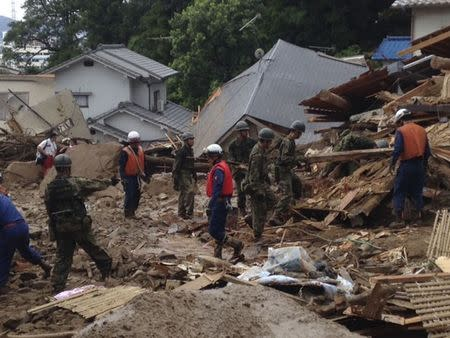 Japan Self-Defense Force soldiers and rescue workers search for survivors as a site where a landslide swept through a residential area at Asaminami ward in Hiroshima, western Japan