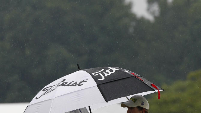 Will Claxton , left, keeps away from the rain as he lines up a putt on the first green during the final round of the Wyndham Championship golf tournament in Greensboro, N.C., Sunday, Aug. 19, 2012. (AP Photo/Gerry Broome)