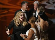 "Singer Adele (L) reacts after accepting the award for best original song for ""Skyfall"" with Paul Epworth (rear) from cast members of the film Chicago at the 85th Academy Awards in Hollywood, California, February 24, 2013 REUTERS/Mario Anzuoni"