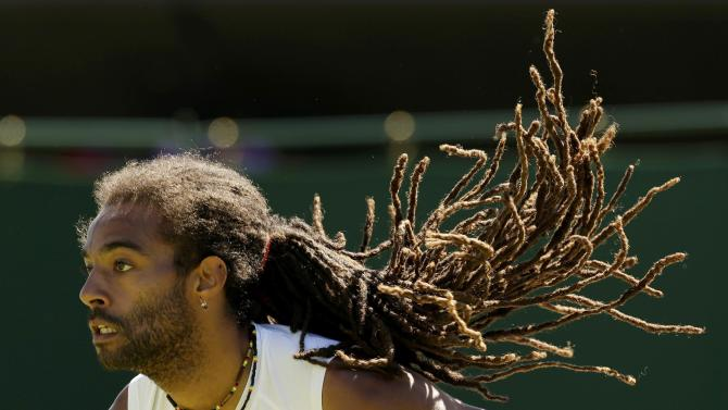 Dustin Brown of Germany servers during his match against Yen-Hsun Lu of Taiwan at the Wimbledon Tennis Championships in London
