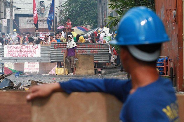 Informal settlers and government demolition crew face off during a demolition operation at Guatemala Street, Barangay San Isidro in Makati City, south of Manila, on 24 September 2012. Around 300 famil
