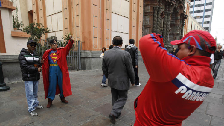 In this photo taken June 14, 2012, Avelino Chavez, wearing his signature Superman costume, poses for pictures with tourists in downtown Lima, Peru. Chavez, 52, took on the Superman persona 15 years ago, when he lost his job as a security guard, and says he has had work ever since. Chavez also says he only earns about $160 US dollars per month, but that he has the strength of a superhero.  Chavez currently works to promote a travel agency. (AP Photo/Martin Mejia)