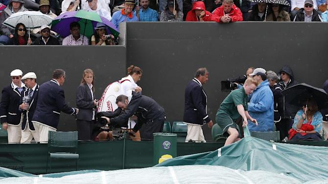 Andrea Petkovic of Germany, rear center, makes her way off court as play is suspended due to rain in her women's single match against Eugenie Bouchard of Canada at the All England Lawn Tennis Championships in Wimbledon, London, Saturday, June 28, 2014. (AP Photo/Alastair Grant)