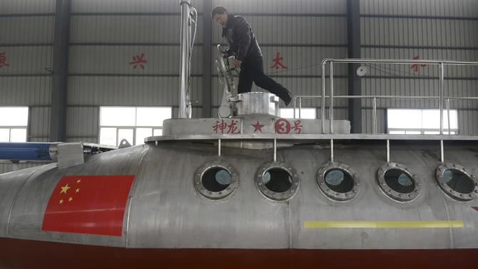 """Zhang, a 62-year-old retired prison guard, enters his homemade submarine named """"Shenlong-3"""" at a factory in Fuyang"""