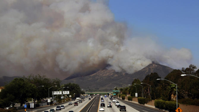 Smoke billows over along U.S. 101 near Thousand Oaks, Calif. on Thursday, May 2, 2013.  Authorities have ordered evacuations of a neighborhood and a university about 50 miles west of Los Angeles where a wildfire is raging close to subdivisions. The blaze on the fringes of Camarillo and Thousand Oaks broke out Thursday morning and was quickly spread by gusty Santa Ana winds. Evacuation orders include California State University, Channel Islands. (AP Photo/Nick Ut)