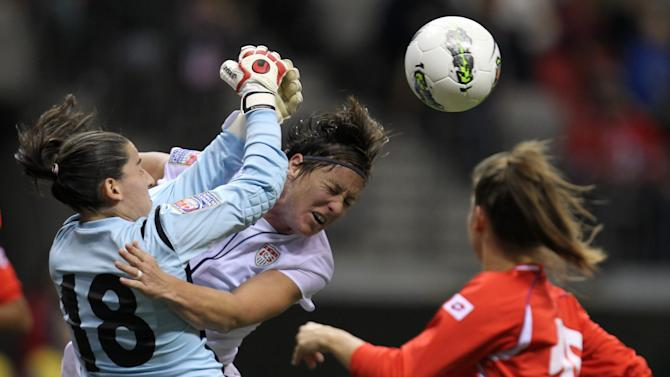 United States' Abby Wambach, center, crashes into Costa Rica goalkeeper Erika Miranda, left, during the first half of CONCACAF women's Olympic qualifying soccer game action at B.C. Place in Vancouver, British Columbia, Friday, Jan. 27, 2012. (AP Photo/The Canadian Press, Jonathan Hayward)