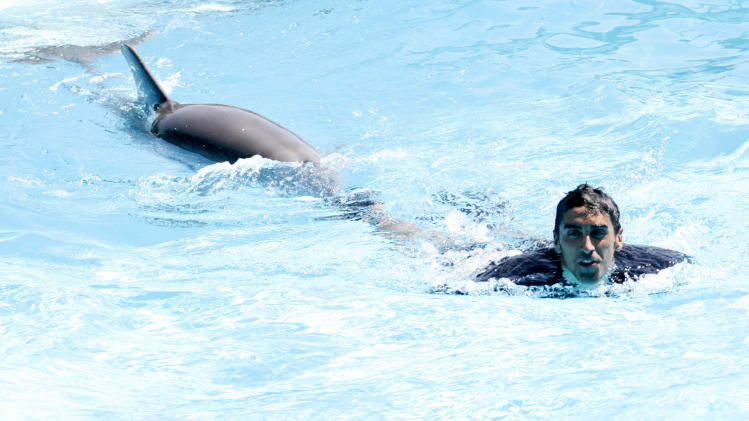 Italian two-time world champion in the 100-meter freestyle Filippo Magnini plays with a dolphin during a performance at Zoomarine's aquatic amusement park in Torvaianica, near Rome, Thursday, Sept. 8, 2011. The captain of the Italian national swimming team lost Thursday against King, 19, and Leah, 9, at an event in Torvaianica. The dolphins had to swim about twice as many lengths as Magnini, but even so, they overtook him. (AP Photo/Riccardo De Luca)