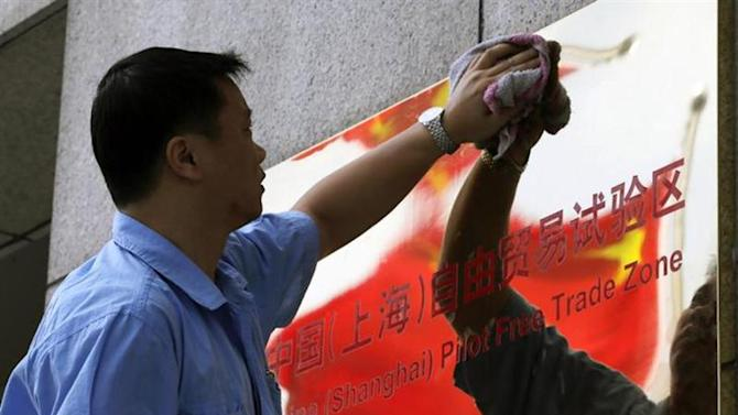 A reflection of the Chinese national flag is seen in a sign for the new China (Shanghai) Pilot Free Trade Zone, as a worker cleans it, in Shanghai, September 29, 2013. REUTERS/Stringer