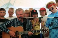 In this April 17, 1998 photo, Doc Watson performs with kids on stage at the MerleFest in Wilkesboro, N.C. Watson, the Grammy-award winning folk musician whose lightning-fast style of flatpicking influenced guitarists around the world for more than a half-century, died Tuesday, May 29, 2012 at a hospital in Winston-Salem, according to a hospital spokeswoman and his management company. He was 89. (AP Photo/The Charlotte Observer, Catherine Bauknight)