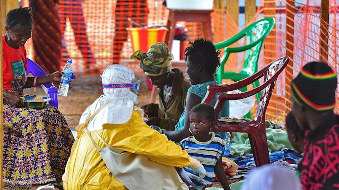 An MSF medical worker feeds an Ebola child victim at an MSF facility in Kailahun, Sierra Leone on August 15, 2014
