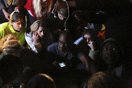 People listen to a radio as the death of former South African President Mandela is announced in Houghton