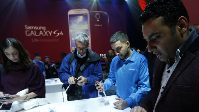 Attendees try out the new Samsung Galaxy S 4 during the Samsung Unpacked event at Radio City Music Hall, Thursday, March 14, 2013 in New York.  (AP Photo/Jason DeCrow)