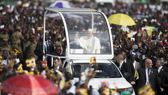 Pope Francis waves to the crowd while on his way to meet youths at the Kololo ceremonial grounds in Uganda's capital Kampala