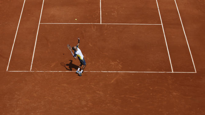 Linesmen watch France's Jo-Wilfried Tsonga serving the ball to Slovenia's Aljaz Bedene during their first round match of the French Open tennis tournament at the Roland Garros stadium Monday, May 27, 2013 in Paris. Tsonga won 6-2, 6-2, 6-3. (AP Photo/Michel Spingler)