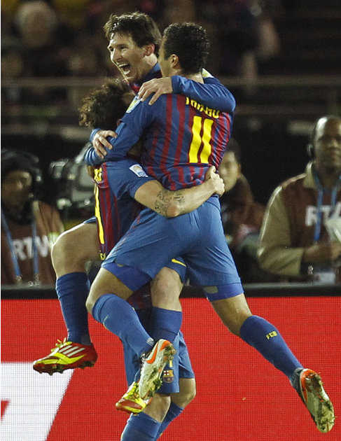 Spain's FC Barcelona midfielder Lionel Messi, top and Thiago Alcantara (11) celebrate with  Cesc Fabregas, bottom, who scores a goal against Brazil's Santos FC during the final at the Club World Cup s