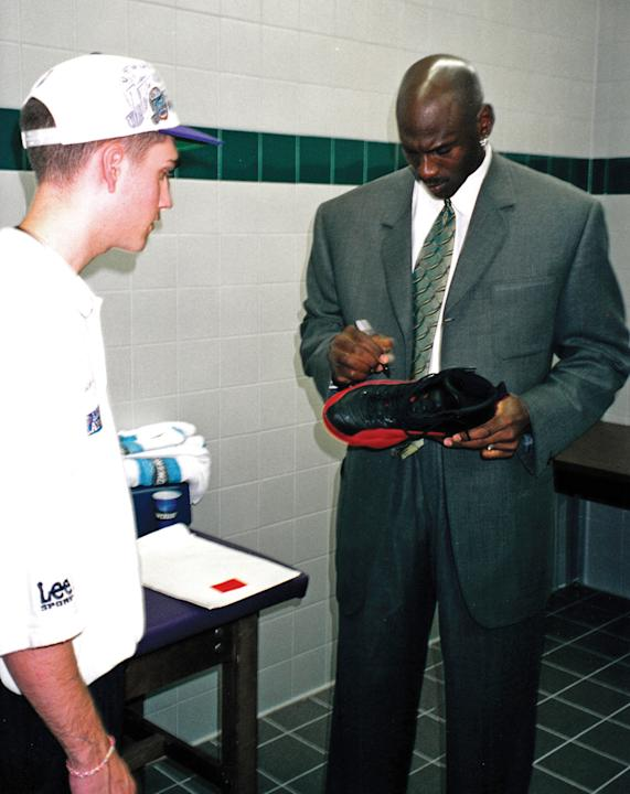 This June 11, 1997 image provided by Grey Flannel Auctions shows Michael Jordan autographing his shoes from the famous 'flu' game of the 1997 NBA Finals, for ball boy Preston Truman, left, aft