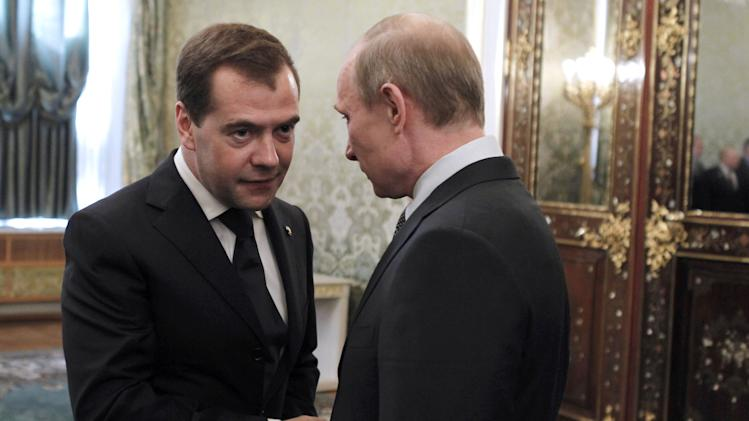 Russian President Dmitry Medvedev, left, and President-elect, Prime Minister Vladimir Putin shake hands at a meeting with government officials and lawmakers in the Kremlin in Moscow, Saturday, May 5, 2012. (AP Photo/RIA-Novosti, Dmitry Astakhov, Presidential Press Service)