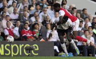 Tottenham Hotspur's Emmanuel Adebayor, left, grapples with Arsenal's Alex Song during their English Premier League soccer match at White Hart Lane stadium, London, Sunday, Oct. 2, 2011. (AP Photo/Tom Hevezi)