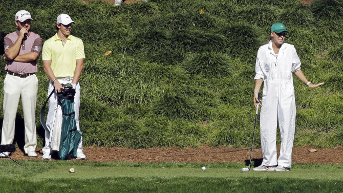Graeme McDowell, left, of Northern Ireland, and Rory McIlroy, of Northern Ireland, watch as tennis player Caroline Wozniacki prepares to tee off on the ninth hole during the par three competition before the Masters golf tournament Wednesday, April 10, 2013, in Augusta, Ga. (AP Photo/David J. Phillip)