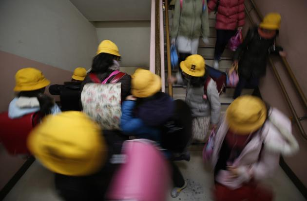 Students walk down the stairs as they evacuate during an earthquake simulation exercise at an elementary school in Tokyo
