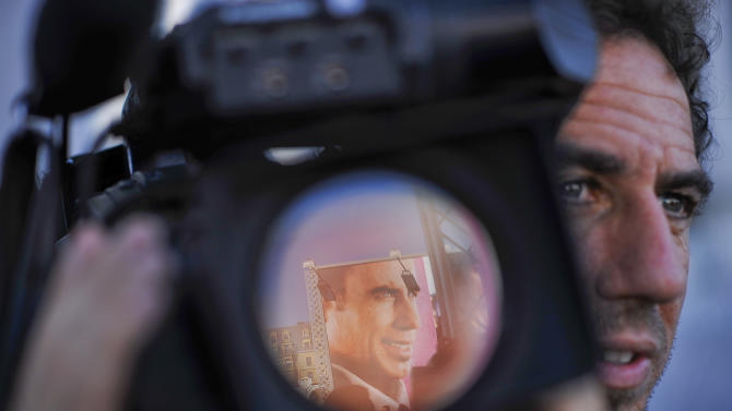 The portrait of U.S. actor John Travolta, one Award of San Sebastian Film Festival, is reflected in the lens of a camera , a day before the beginning of the 60th San Sebastian Film Festival Cinema in San Sebastian, northern Spain, Thursday Sept. 20, 2012. The San Sebastian Film Festival, the oldest and most prestigious in the Spanish speaking world, opens tomorrow with a strong focus on European and American movies. (AP Photo/Alvaro Barrientos)