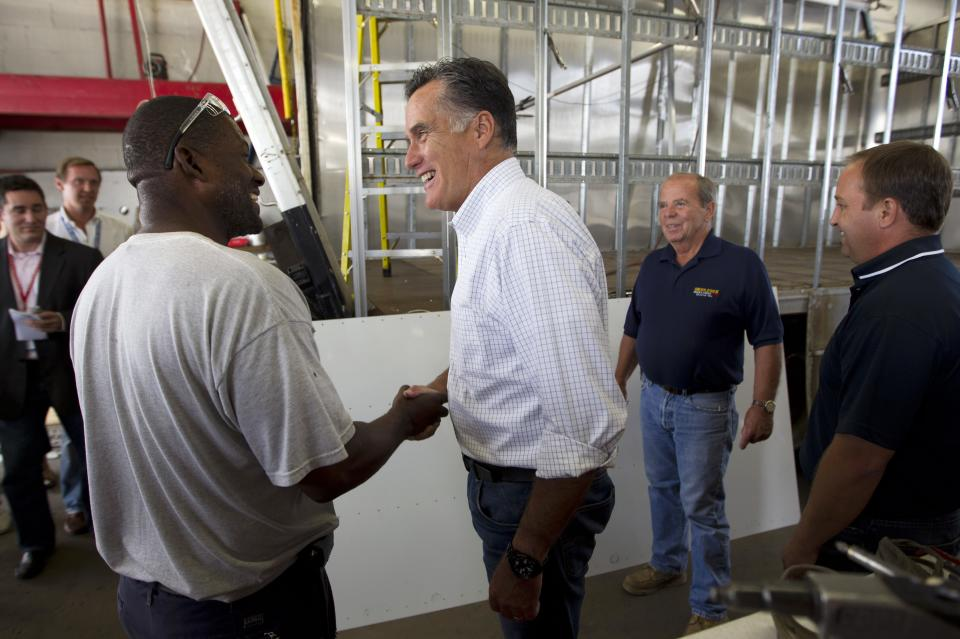 Republican presidential candidate, former Massachusetts Gov. Mitt Romney, center, shakes hands with Rodney Hollis, an employee of Middlesex Truck and Coach, during a campaign stop on Thursday, July 19, 2012 in Roxbury, Mass.  (AP Photo/Evan Vucci)