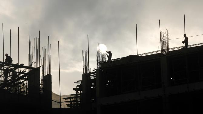 Labourers work as the sun sets at  construction site of new urban complex near Hanoi