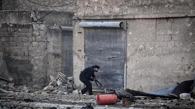 In this Wednesday, Dec. 5, 2012 photo, a Free Syrian Army fighter runs for cover during heavy clashes with government forces, not pictured, in Aleppo, Syria. (AP Photo/Narciso Contreras)