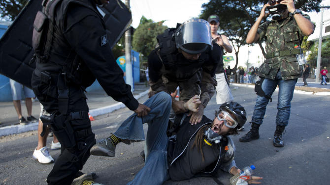 Riot police detain a man during a demonstration in Belo Horizonte, Brazil, Wednesday, June 26, 2013. Brazilian anti-government protesters in part angered by the billions spent in World Cup preparations and police clashed Wednesday near the stadium hosting a Confederations Cup football match, with tens of thousands of demonstrators trying to march on the site confronting police firing tear gas and rubber bullets.(AP Photo/Victor R. Caivano)
