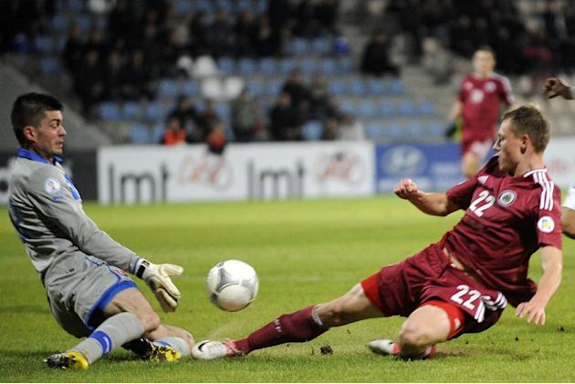 Latvia's Eduards Visnakovs, right, vies for the ball with Slovakia's goalkeeper Matus Kozacik during a World Cup 2014 Group G qualification match in Riga, Latvia, on Tuesday. October 15, 2013