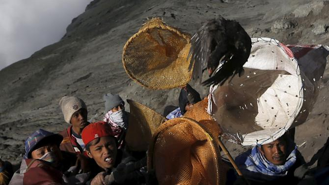 Villagers hold nets as try to catch offerings thrown by Hindu worshippers during the Kasada Festival at the crater of Mount Bromo, in Probolinggo