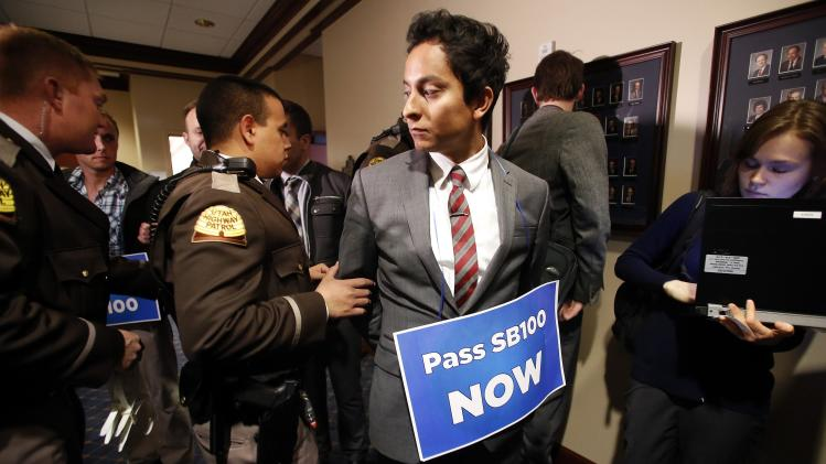 LGBT rights activist are detained by members of the Utah Highway Patrol after blocking a Senate committee hearing room at the Utah State Capitol
